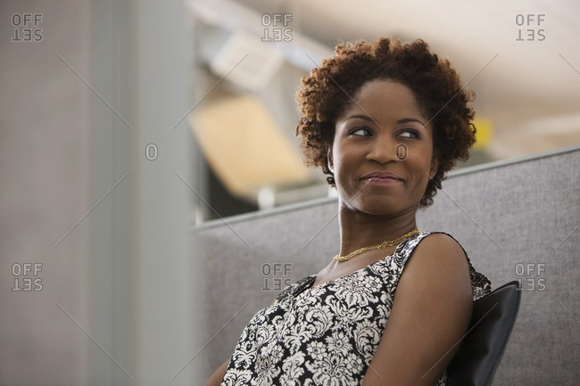 Black businesswoman sitting in office cubicle