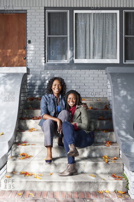 Black mother and daughter sitting on front stoop