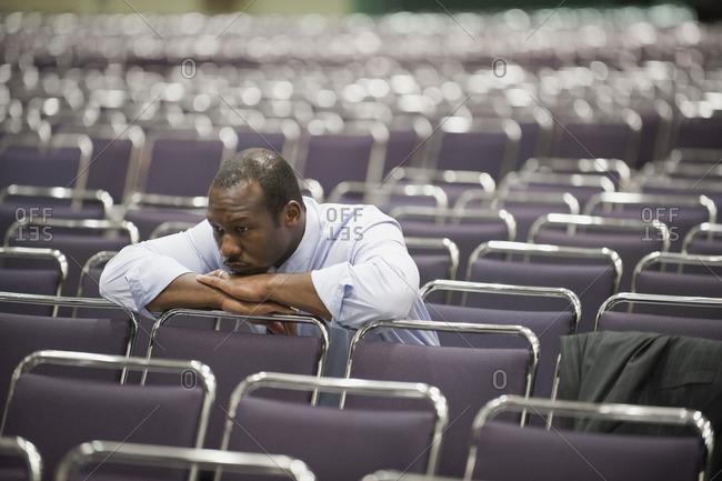 Impatient Black businessman waiting in empty conference center