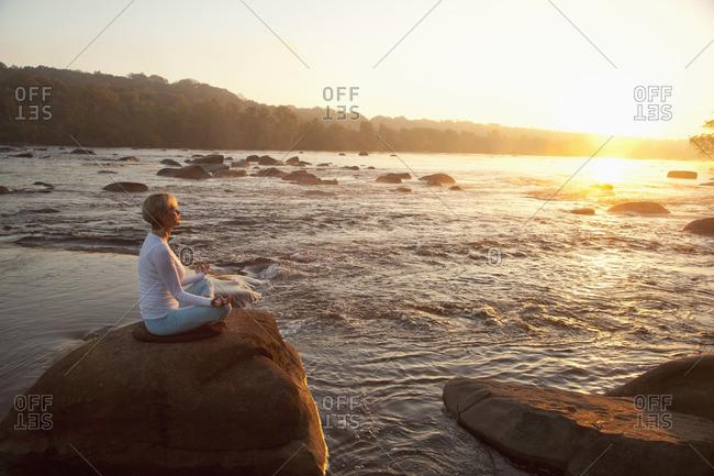 Caucasian woman practicing yoga on rock near ocean