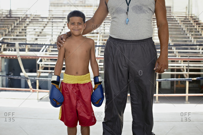 Hispanic trainer standing with boy in boxing gear