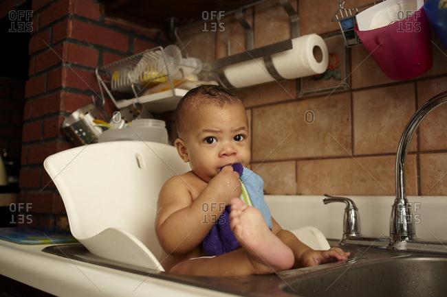 Mixed race baby girl bathing in sink