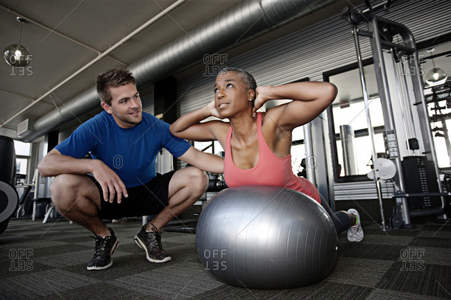 Personal trainer helping woman in health club