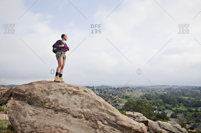 Black hiker standing on rock in remote area