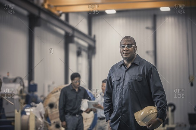 African American worker standing in factory