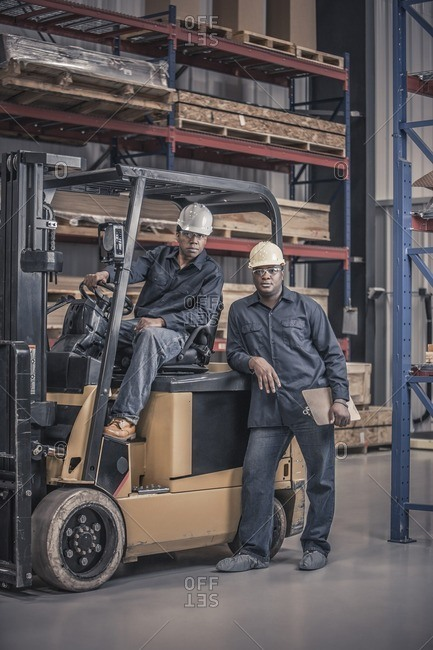 African American workers with forklift in factory