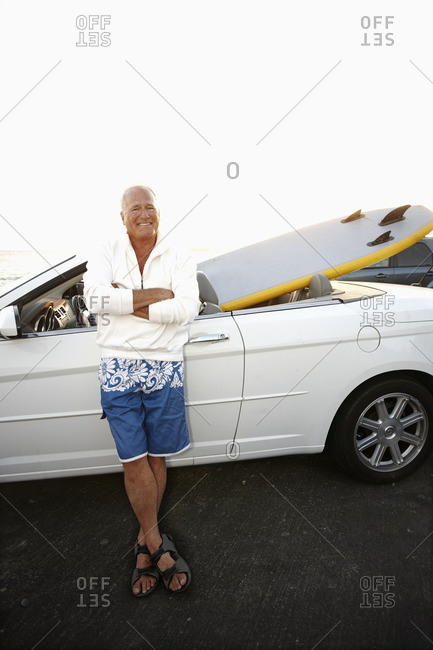 Caucasian man standing with car and paddleboard