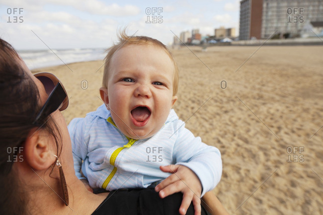Caucasian mother holding baby boy on beach