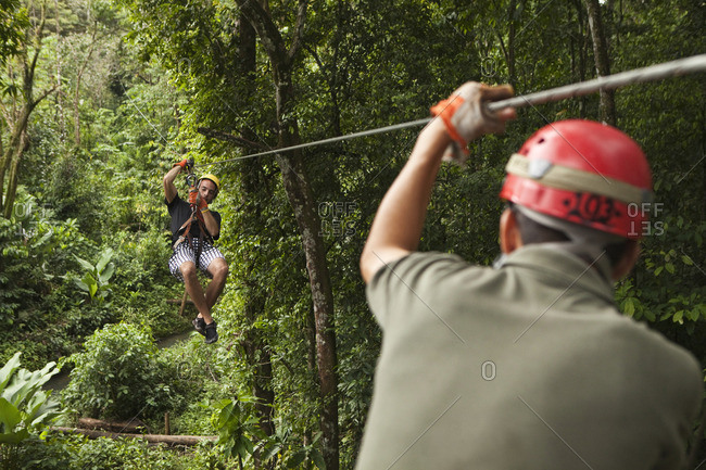 Caucasian man on zip line in forest