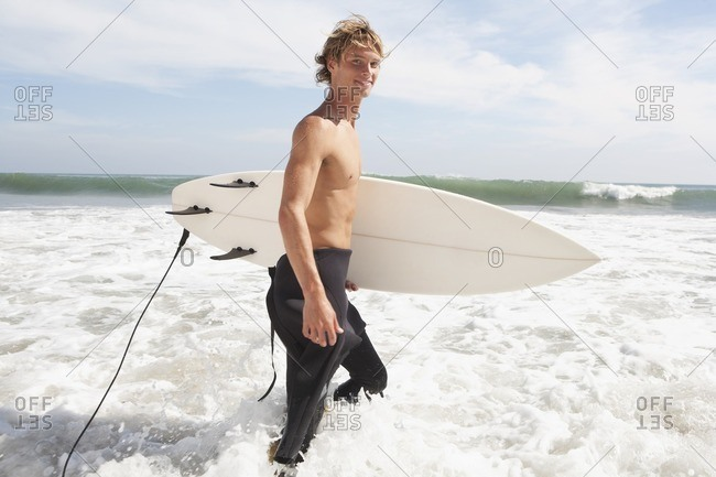 Caucasian surfer carrying surfboard