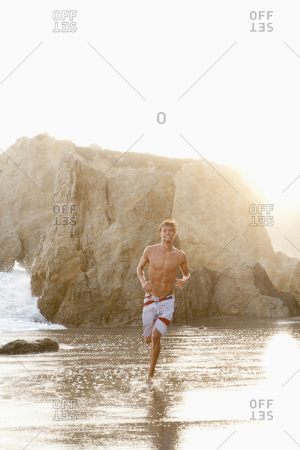 Caucasian man running on beach