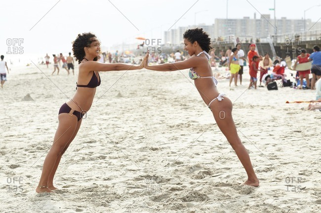Mixed race friends playing on beach