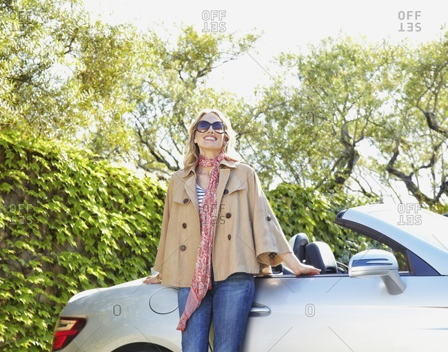 Woman leaning on convertible