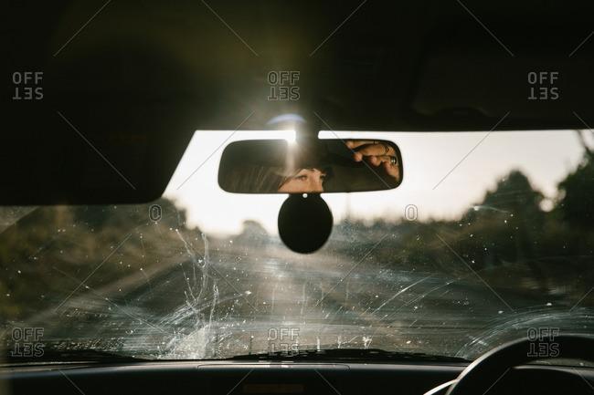 Woman shielding eyes from road glare