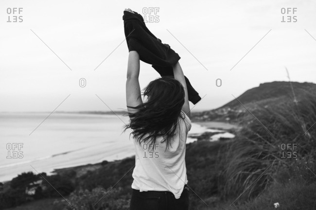 Woman taking off sweater at coast