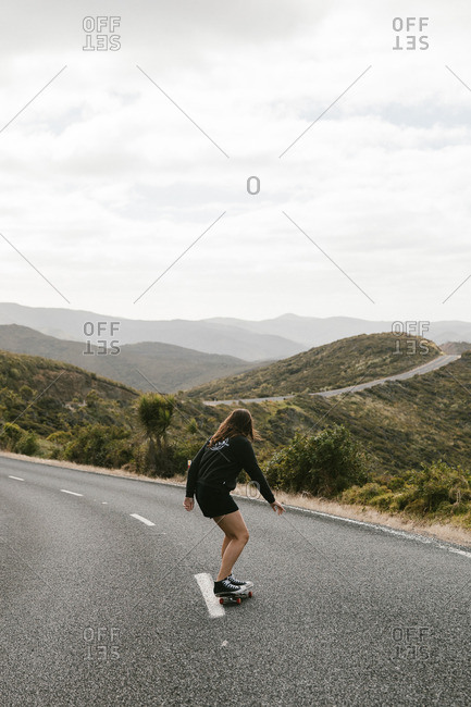Woman skateboarding down rural highway