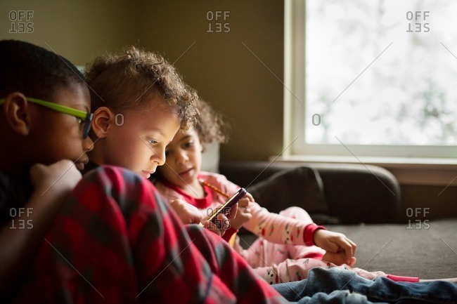 Three kids watching a phone together