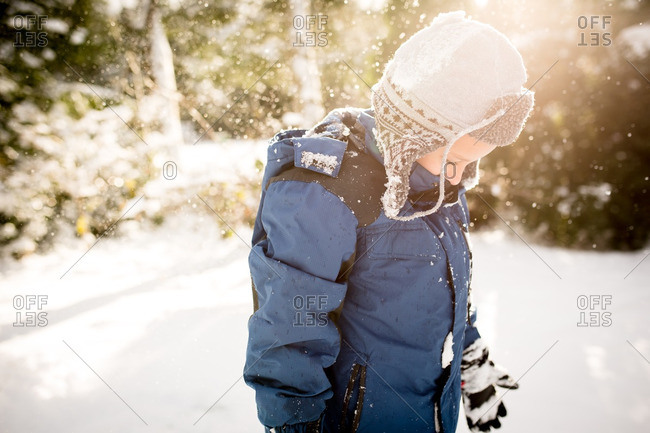 Boy in sunlight during snow fall