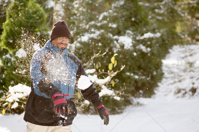 Man throwing snowball in winter