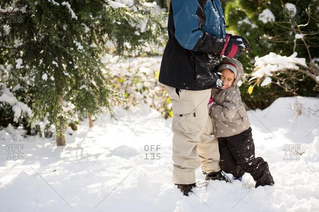 Child hugging dad's leg in winter