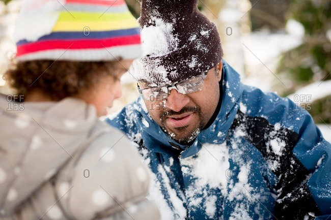 Man covered in snow by daughter