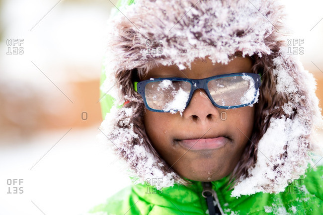 Boy with glasses covered in snow