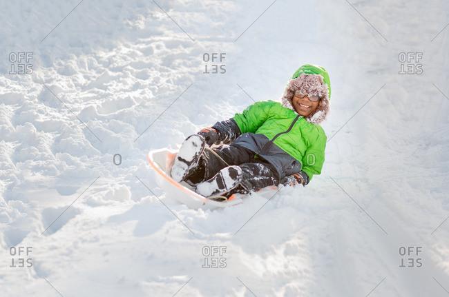 African American boy sledding