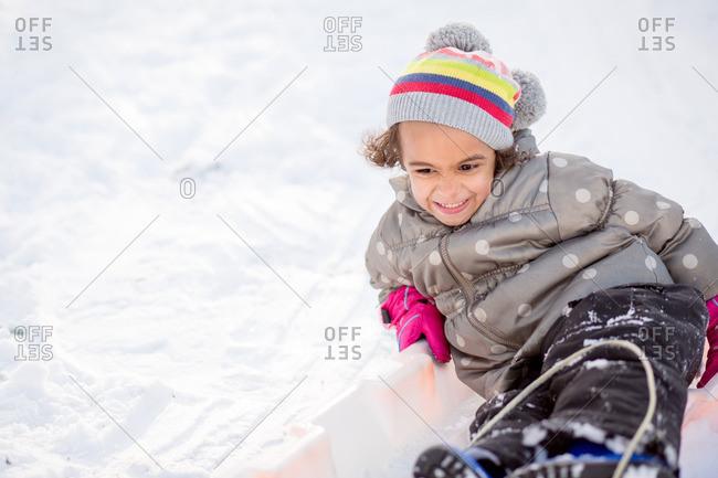 A smiling girl going sledding