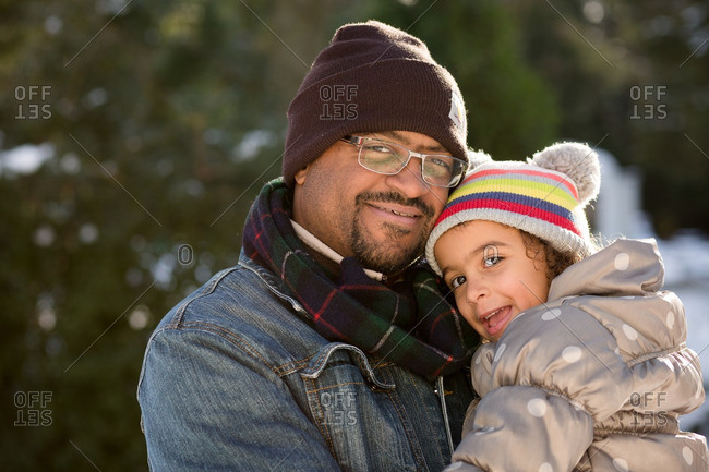 Man holding daughter in winter setting