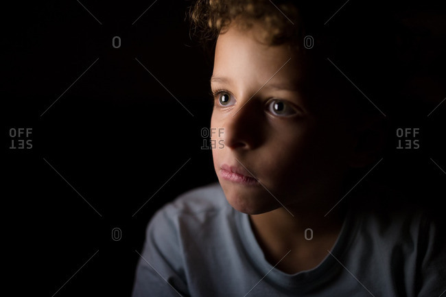 Boy with curly hair looking away