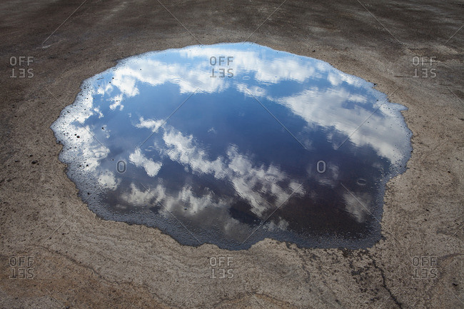 Rain drops falling onto a large puddle. A reflection of sky and clouds.