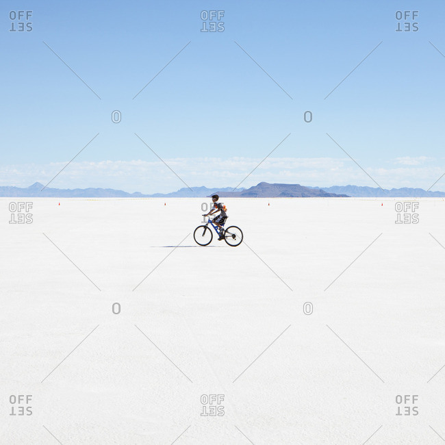 Boy riding bike on salt flats, during Speed Week