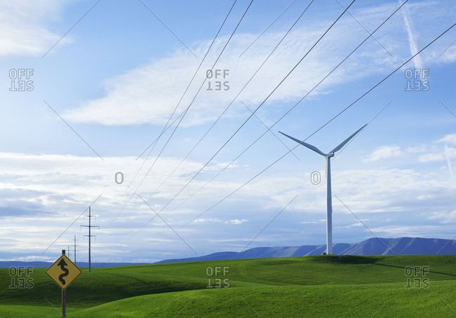 Wind turbines on a grassy hilltop, and a road sign warning of a Winding Road. Green sustainable energy production.