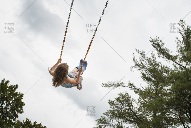 A girl on a rope swing, high in the air