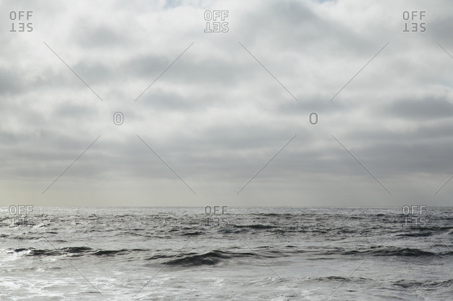 View from the beach over the water, to the horizon, and the seascape at dusk