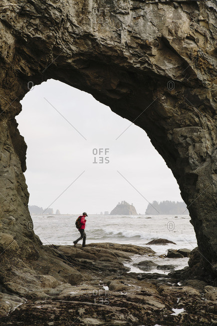 Man hiking on the beach at Hole-in-the-Rock on Rialto Beach