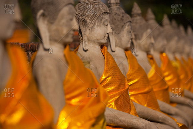 Wat Yai Chai Mongkon, a historic Buddhist temple. Rows of seated Buddha statues, swathed in saffron robes.