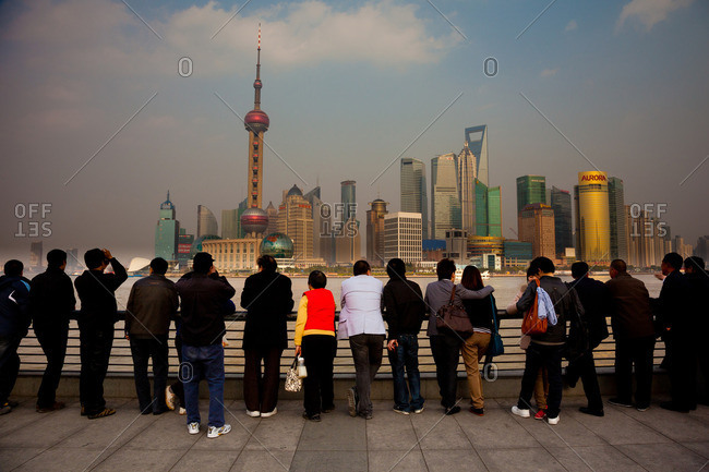 Pudong, Shanghai, China - March 24, 2011: A row of people looking at the Shanghai Pudong skyline