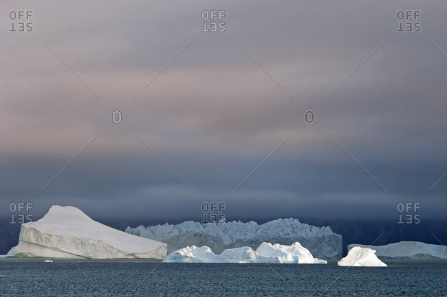 Sunset sky, with heavy cloud and floating icebergs with smooth eroded shapes on the waters of Baffin Island.