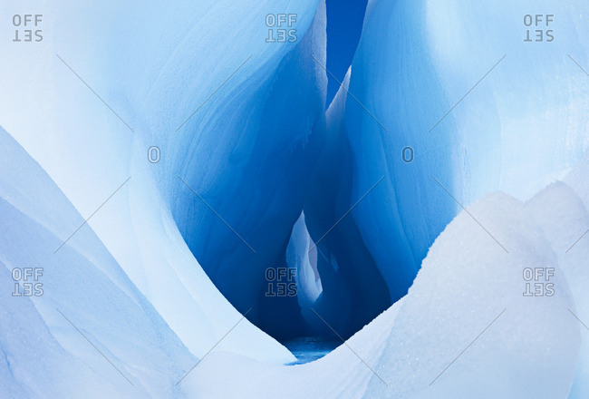Icebergs and ice formations in the Antarctic. A large fissure or hole in the centre of a block of ice, with smooth sides.
