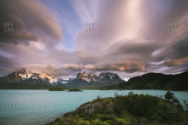 Cloud formations in the skies above the Torres del Paine National Park in Chile. Sunset over the waters of the sea, and snowcapped peaks.