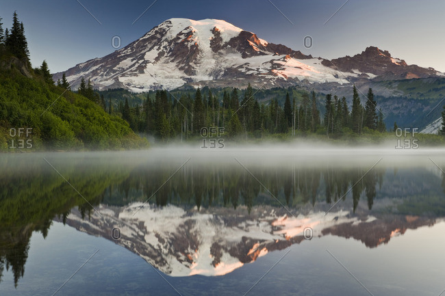 Mount Rainier, a snow capped peak, surrounded by forest reflected in one of many lakes in the Mount Rainier National Park.