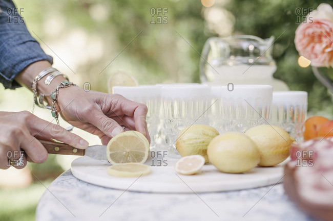 Close up of a woman standing at a table in a garden, slicing lemons for a drink.