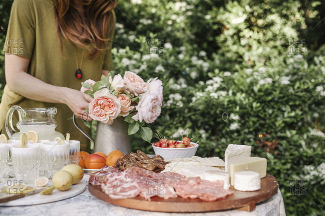 Woman standing at a table in a garden, a vase of pink roses, drinks, a bowl of cherries and a wooden board with cold cuts and cheese.