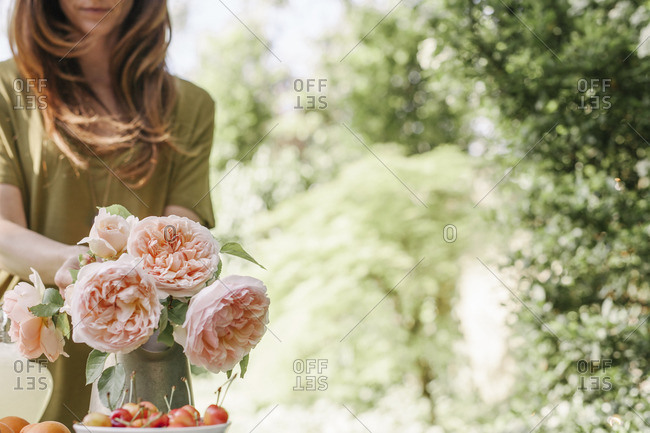 Woman standing at a table in a garden, a vase of pink roses and a bowl of cherries.