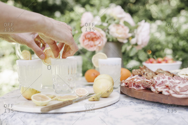 Close up of a woman preparing drinks, a wooden board with cold cuts on a table in a garden.