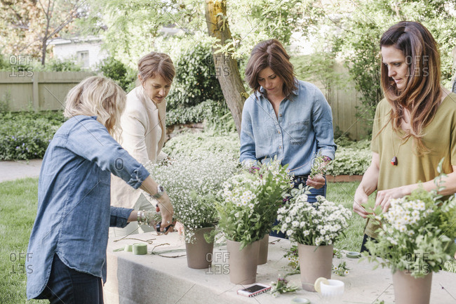 Four women, standing at a table in a garden, making flower wreaths.