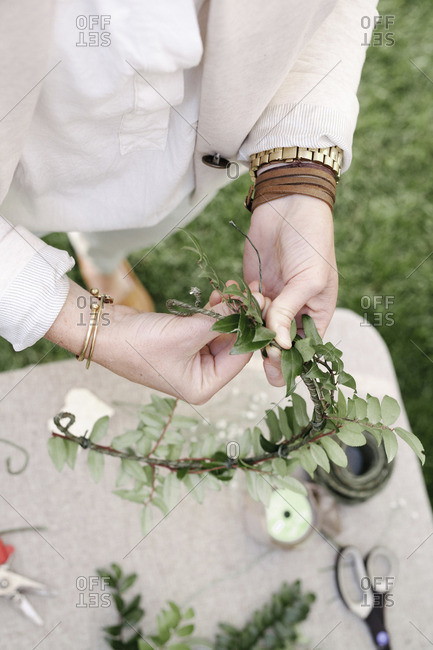 Close up of a woman, standing in a garden, making a flower wreath.