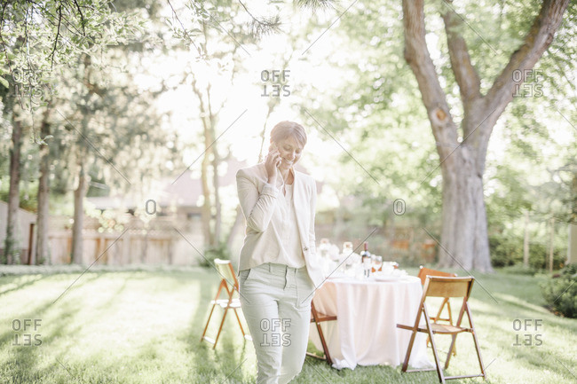 Woman standing in a sunlit garden, talking on her mobile phone.