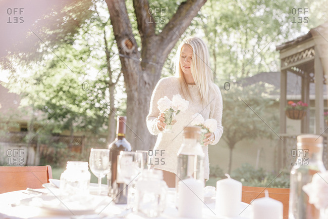 Blond woman setting a table in a garden, candles and vases with pink roses.